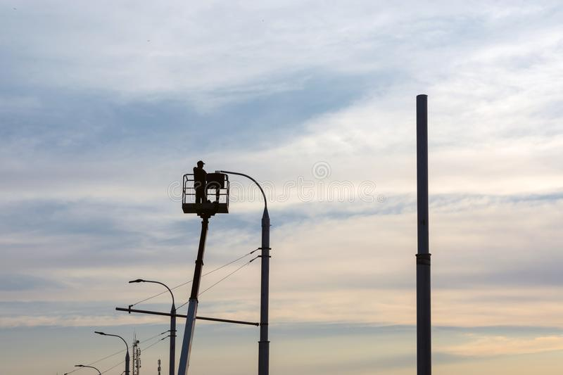 An electrician man sets a lantern on a pole, against the sky, during sunset stock image