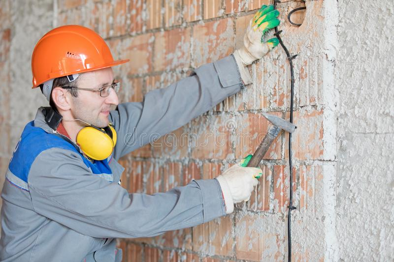 Electrician man worker installing electrical cable at house wall stock photos