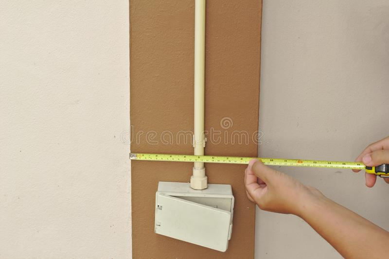 An electrician measured the height of a rectangular white light switch box on the wall stock photo