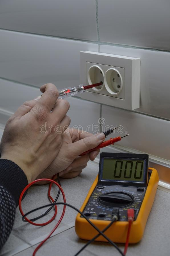 Electrician measurements with multimeter tester stock photography