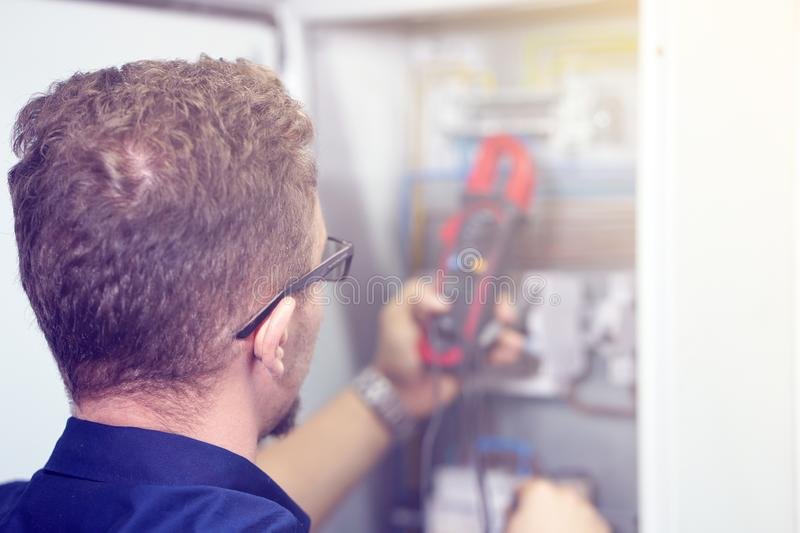 Multimeter is in hands of electrician on background of electrical automation cabinet. An electrician is checking the voltage in stock photography