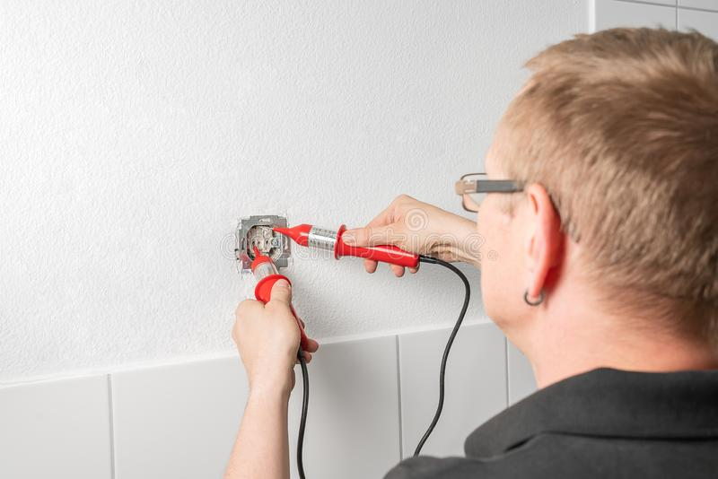 An electrician measures the voltage at a power outlet with a voltage indicator stock images