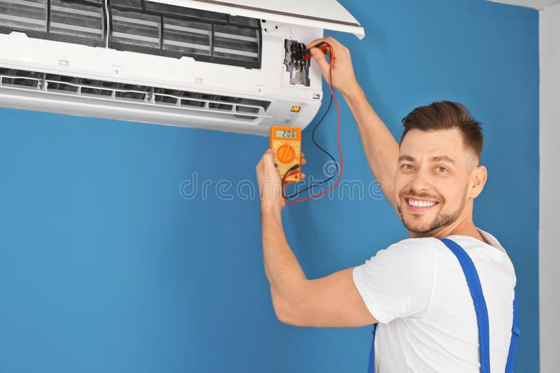 Electrician measuring voltage of air conditioner indoors royalty free stock image