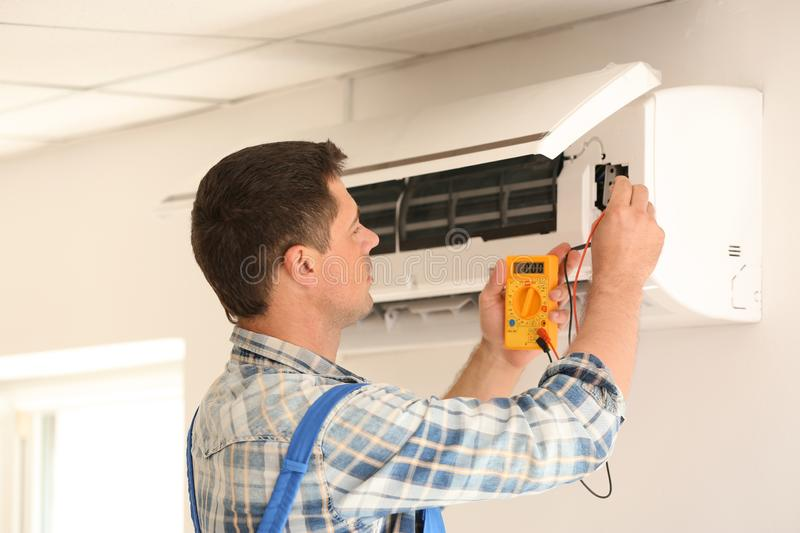 Electrician measuring voltage of air conditioner indoors royalty free stock photography