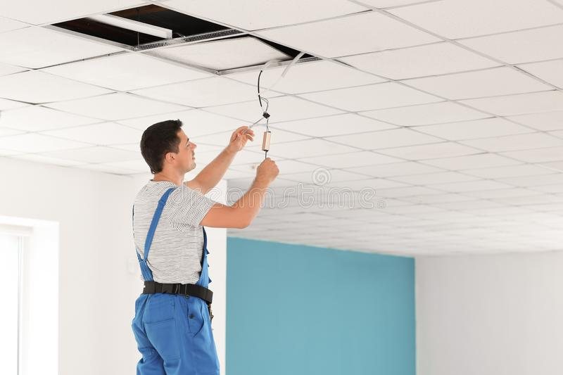 Electrician measuring voltage of cable on ceiling indoors royalty free stock image