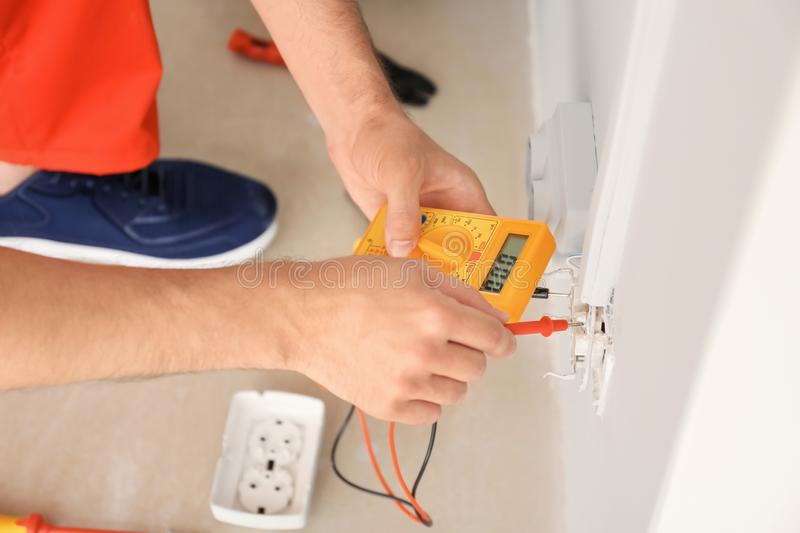 Electrician measuring voltage in socket indoors royalty free stock images