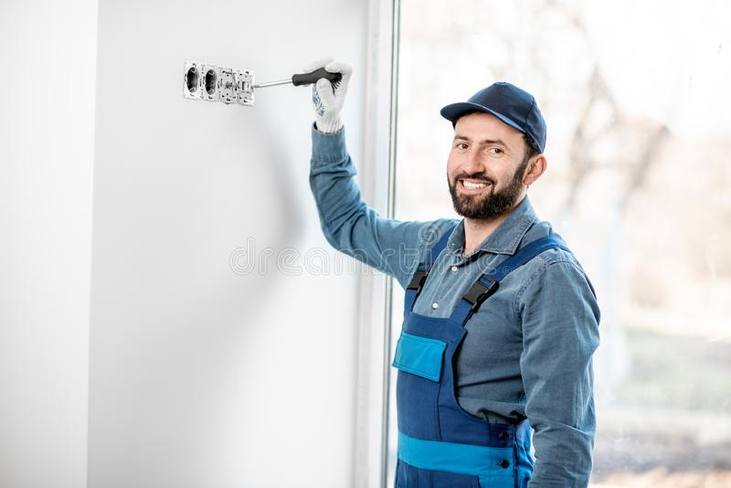 Electrician mounting sockets indoors stock photo