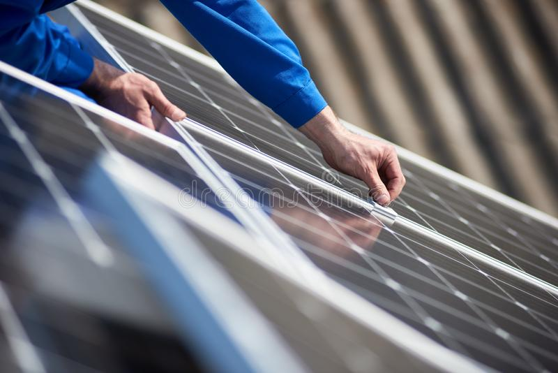 Electrician mounting solar panel on roof of modern house. Male engineer in blue suit installing solar photovoltaic panel system. Close up view of electrician stock photo