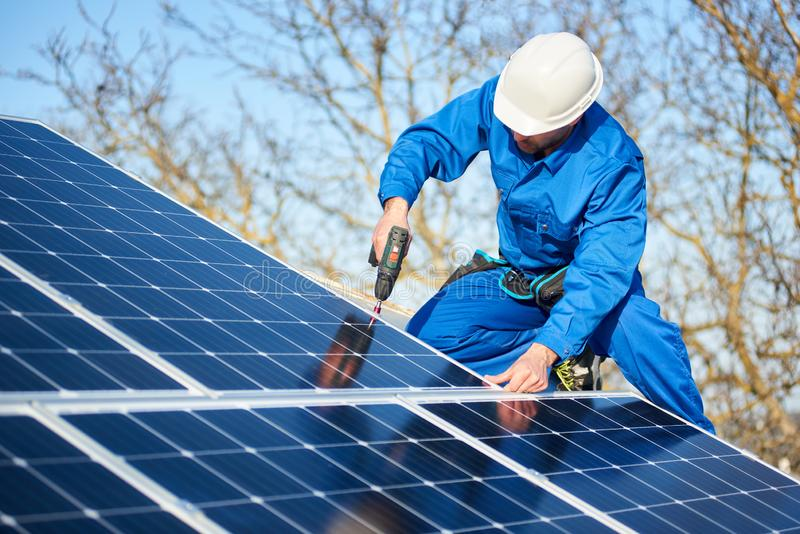 Electrician mounting solar panel on roof of modern house stock images