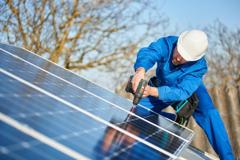 Electrician mounting solar panel on roof of modern house royalty free stock photos