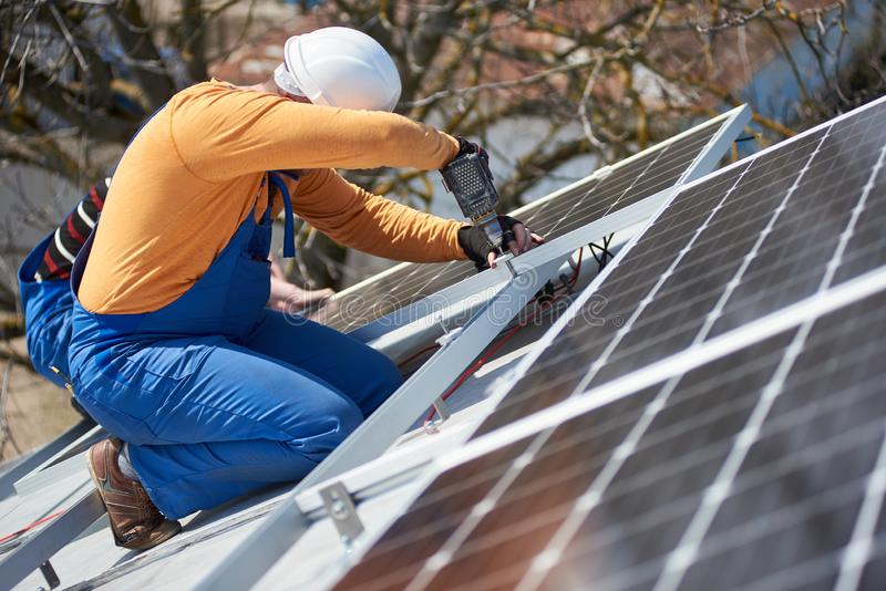 Electrician mounting solar panel on roof of modern house royalty free stock images
