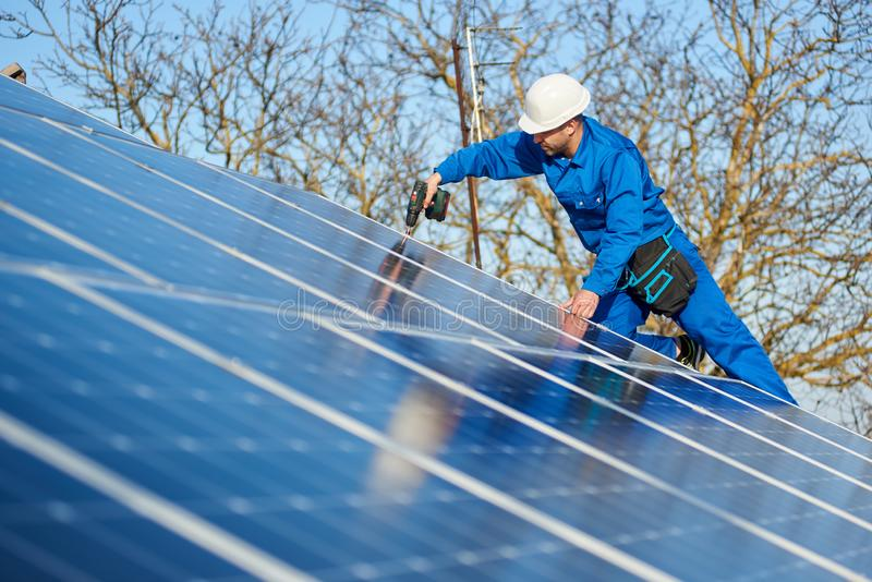 Electrician mounting solar panel on roof of modern house royalty free stock image