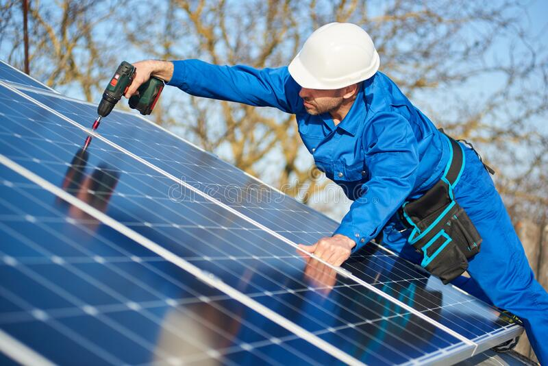 Electrician mounting solar panel on roof of modern house. Man worker in blue suit and protective helmet installing solar photovoltaic panel system using stock photos