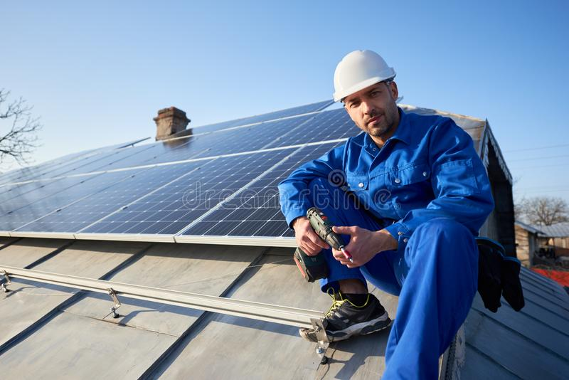 Electrician mounting solar panel on roof of modern house stock photos