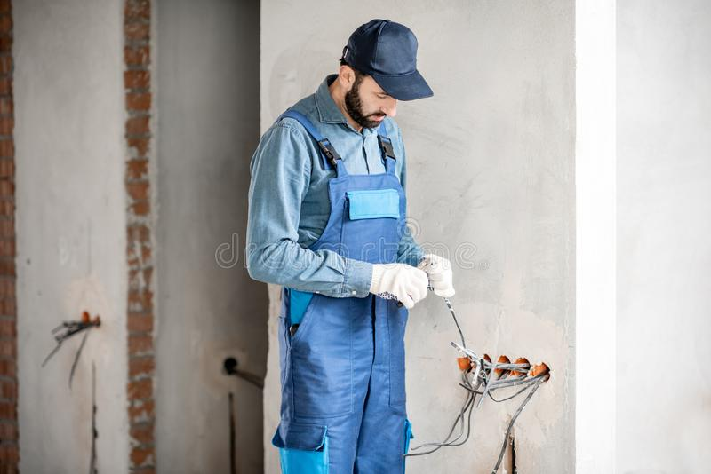 Electrician mounting wiring indoors royalty free stock photo