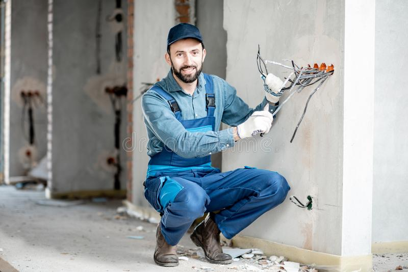 Electrician mounting wiring indoors. Portrait of an electrician mounting wiring for electric sockets on the construction site of a new building indoors royalty free stock photography