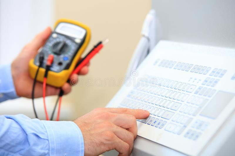 Electrician with multimeter using industrial keypad royalty free stock photo