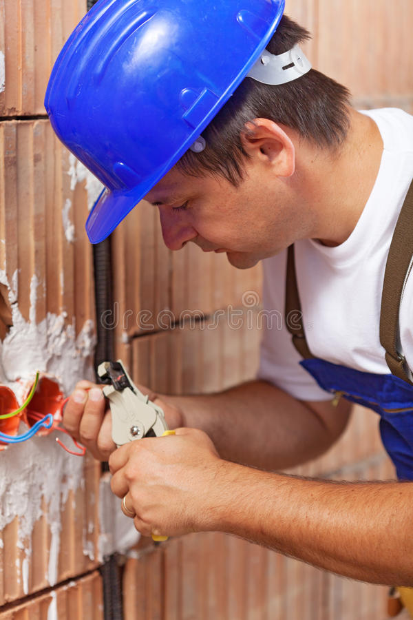 Electrician peeling off wires royalty free stock image