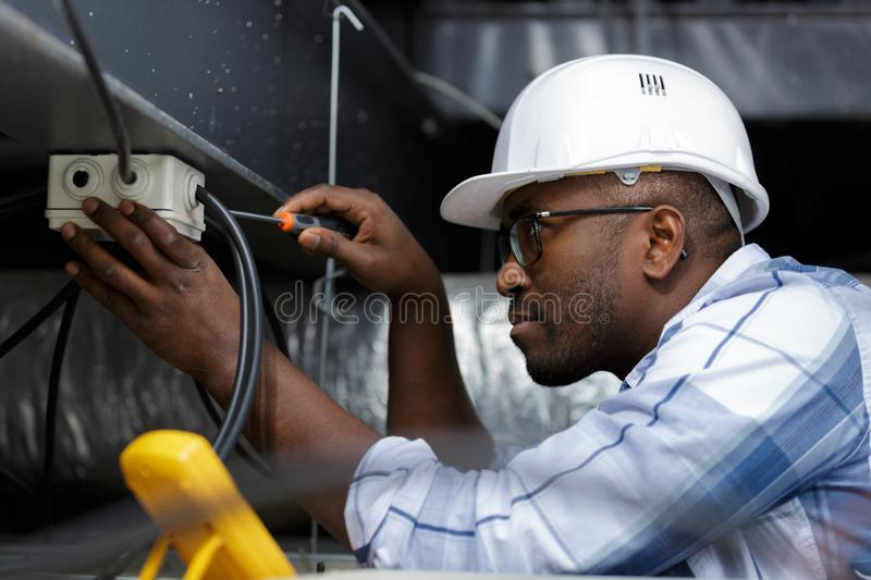 Electrician performs electrical work stock photo