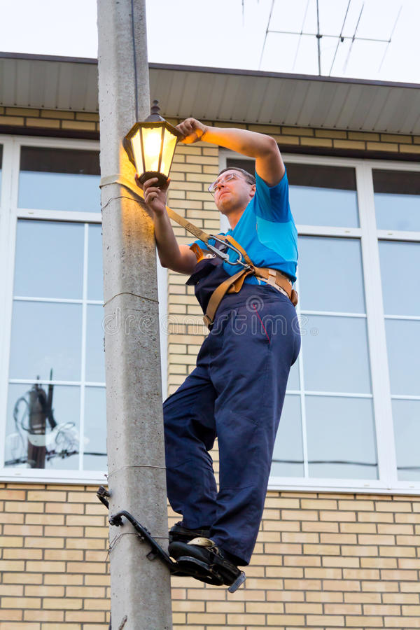 Electrician on a pole. Electrician replace the lamp on a pole royalty free stock photo