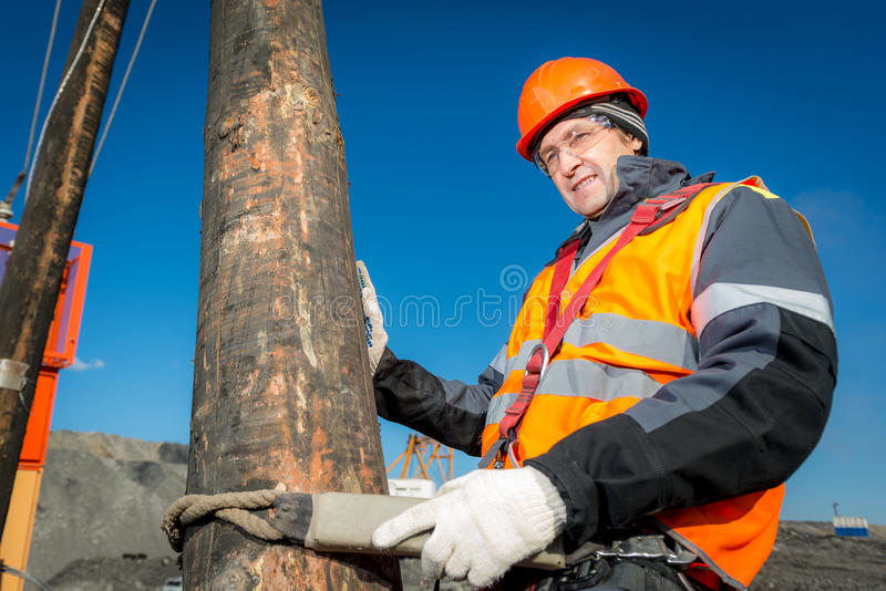 Electrician on a pole against the blue sky stock photography