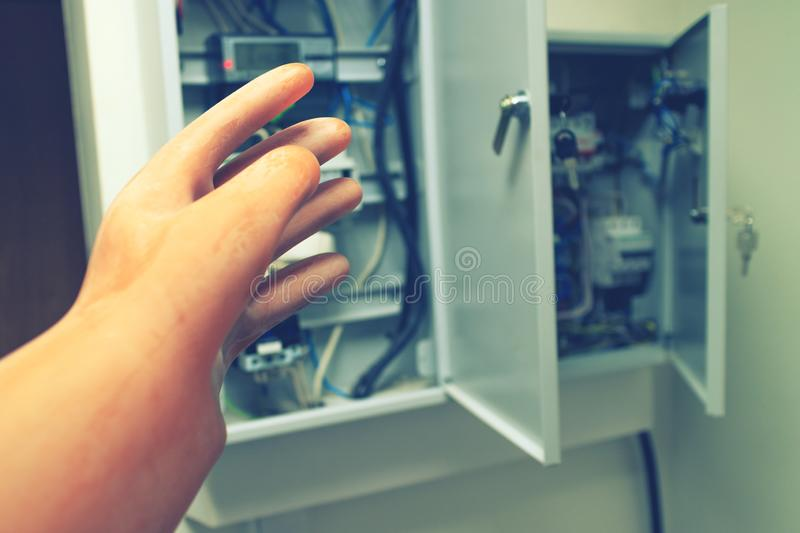 Electrician reaches for the electric wires and electric machines dielectric protective glove royalty free stock photo