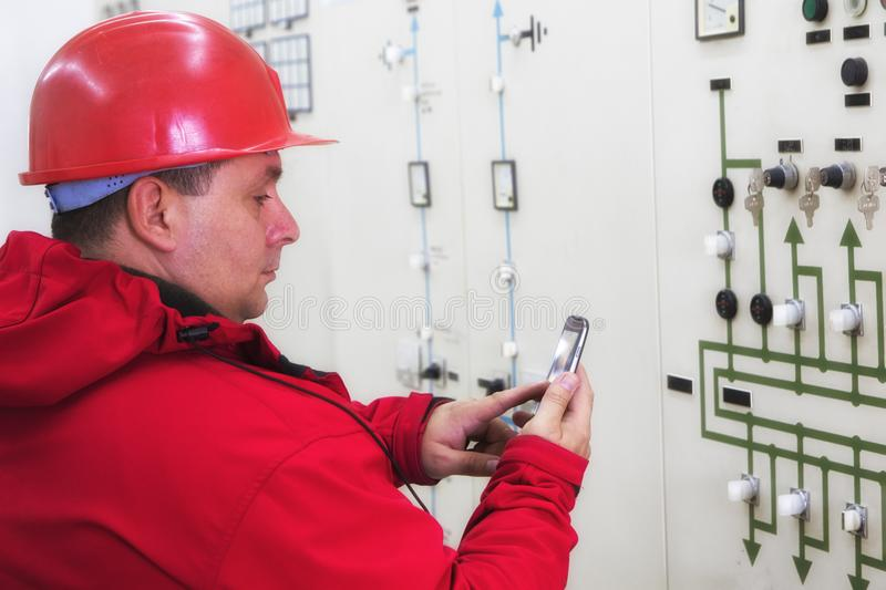 Electrician reading instruments and sending sms in power plant. Technician reading instruments and sending message in power plant control center stock image