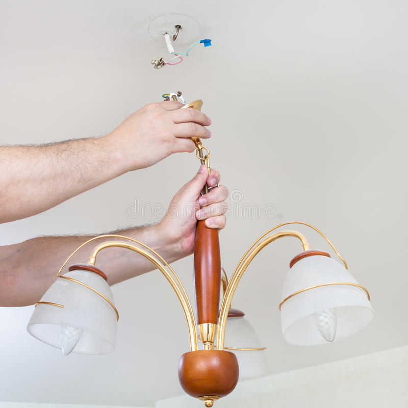 Electrician removes decorative ceiling light royalty free stock image