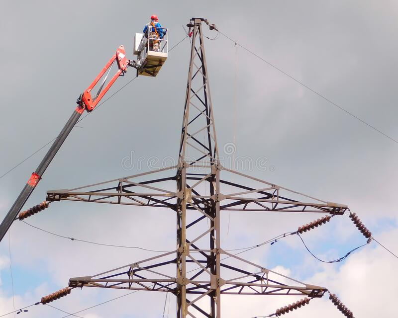 Electrician repair of electric power system on hydraulic platform stock photos