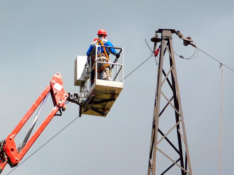 Electrician repair of electric power system on hydraulic platform stock photography