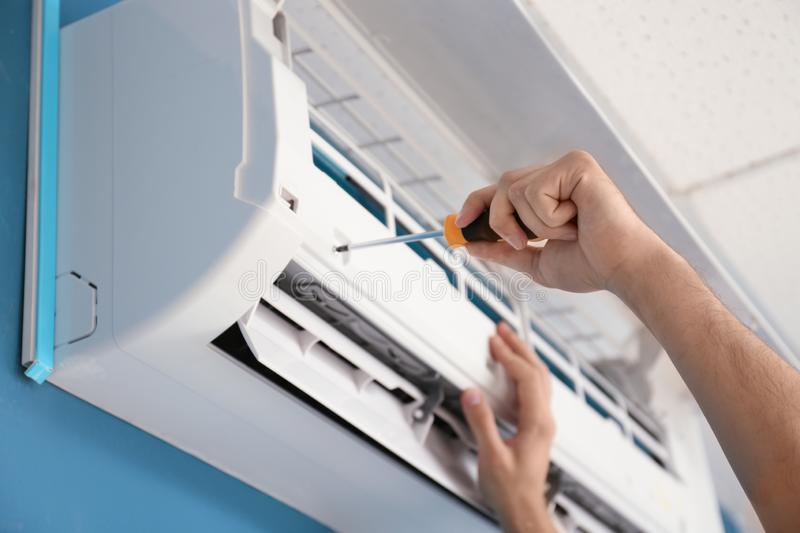Electrician repairing air conditioner indoors, closeup royalty free stock photography