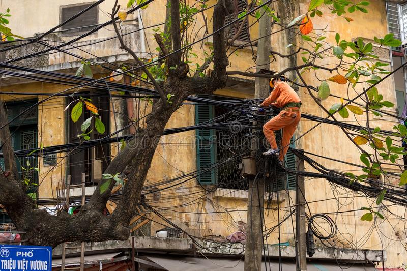 Electrician repairing cables. HANOI, VIETNAM, DECEMBER 16, 2014 : A technician is repairing or checking the messy electrical network in the city of Hanoi stock photography