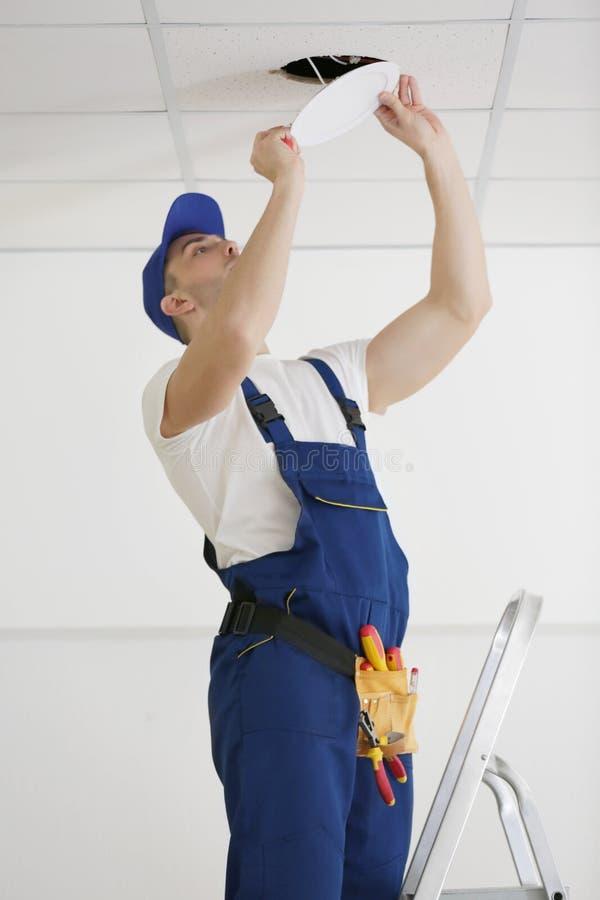 Electrician repairing ceiling light stock photos