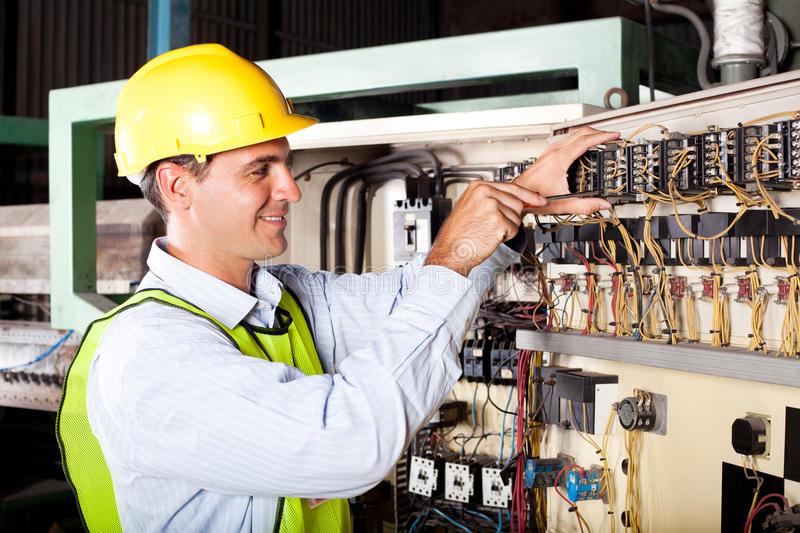 Electrician repairing industrial machine. Male electrician repairing industrial machine control component stock image