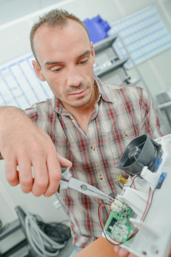 Electrician repairing an item. Young royalty free stock image