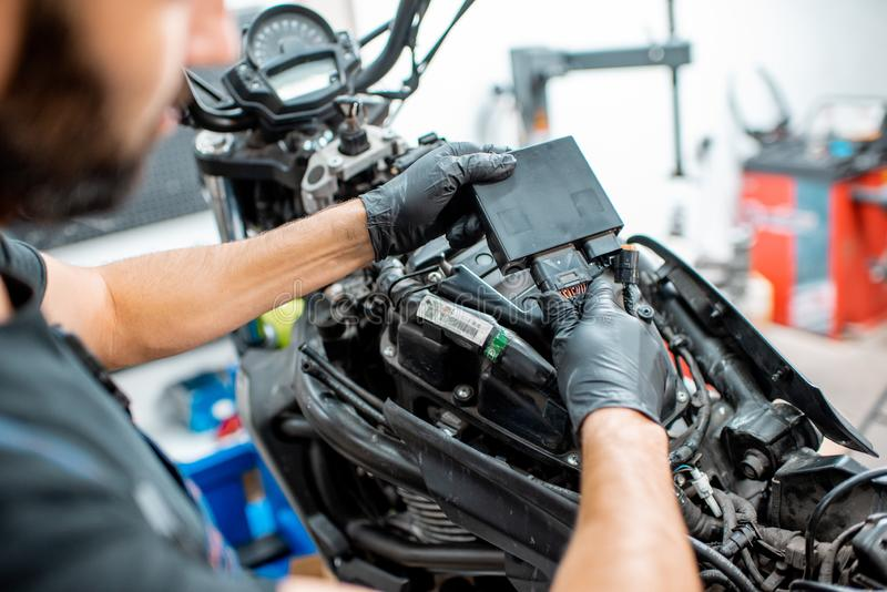 Electrician repairing motorcycle wiring. Electrician or repairman in protective gloves connecting wiring in the motorcycle during a repairment at the workshop royalty free stock photography