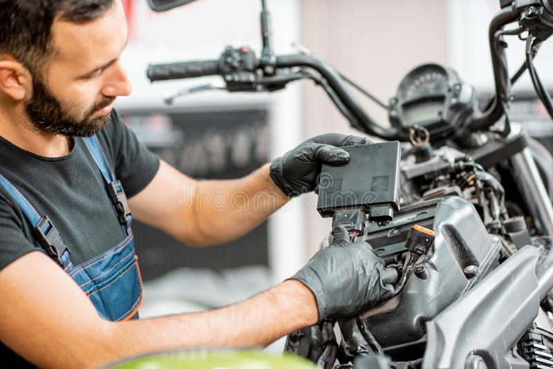 Electrician repairing motorcycle wiring. Electrician or repairman in protective gloves connecting wiring in the motorcycle during a repairment at the workshop stock images
