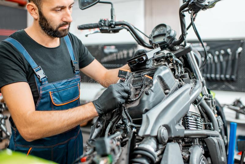 Electrician repairing motorcycle wiring. Electrician or repairman in protective gloves connecting wiring in the motorcycle during a repairment at the workshop royalty free stock image