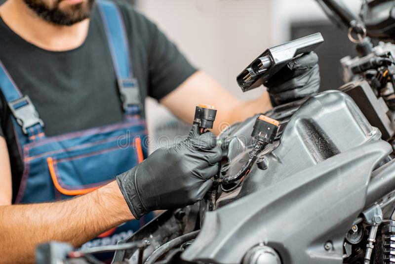Electrician repairing motorcycle wiring. Electrician or repairman in protective gloves connecting wiring in the motorcycle during a repairment at the workshop stock photography