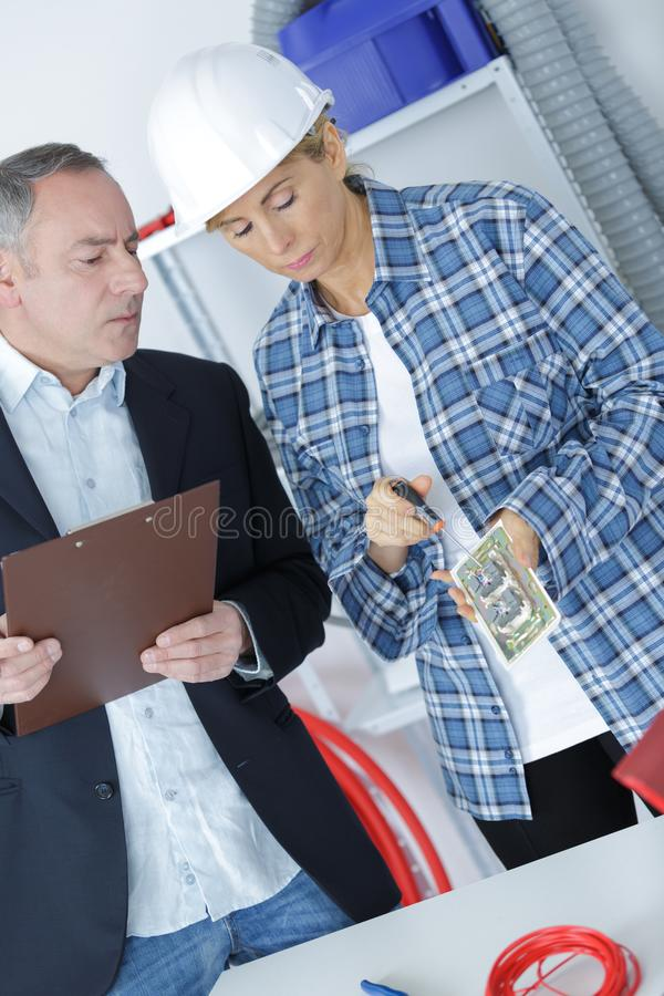Electrician repairing wall socket foreman supervising royalty free stock images