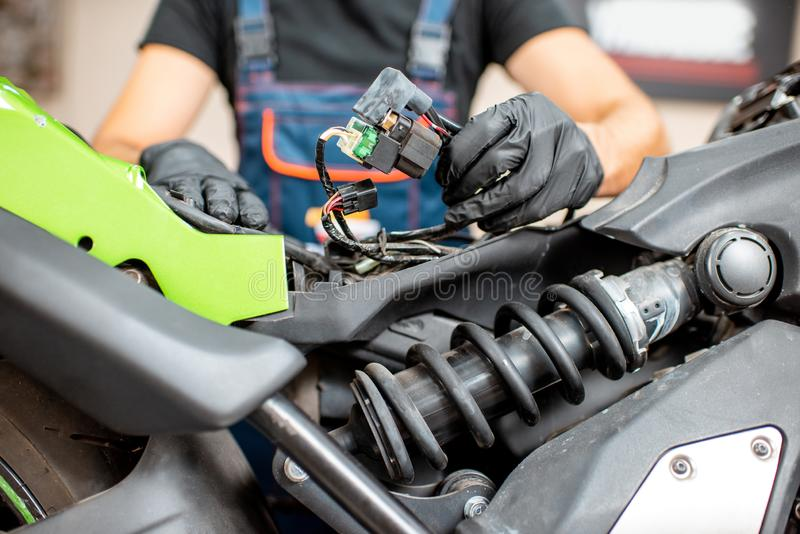 Electrician repairing wiring in the motorcycle royalty free stock photography
