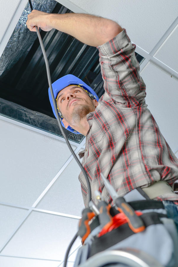 Electrician repairing wiring in an office stock photos