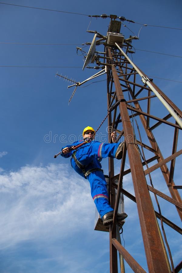 Electrician repairs the radio link on electric power pole royalty free stock image