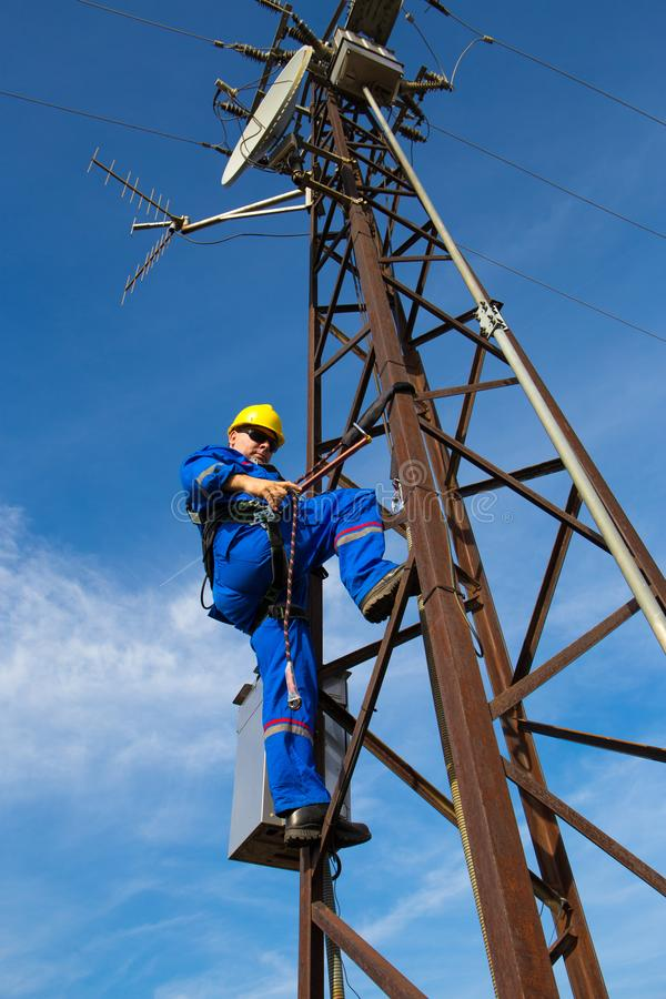 Electrician repairs the radio link on lamppost royalty free stock photo