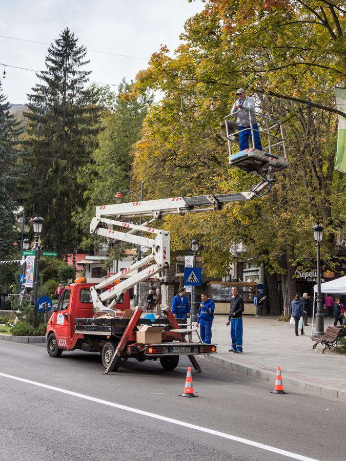 The electrician repairs street lighting on the Boulevard of Carol the First in Sinaia in Romania. Sinaia, Romania, October 05, 2017 : The electrician repairs royalty free stock image