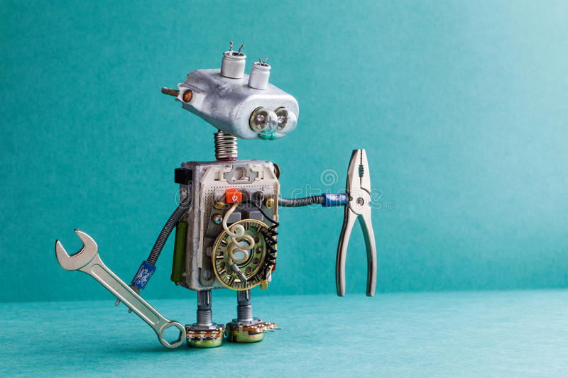 Electrician robot handyman wrench pliers. Mechanic cyborg toy lamp bulb eyes head, electric wires, capacitors vintage royalty free stock images
