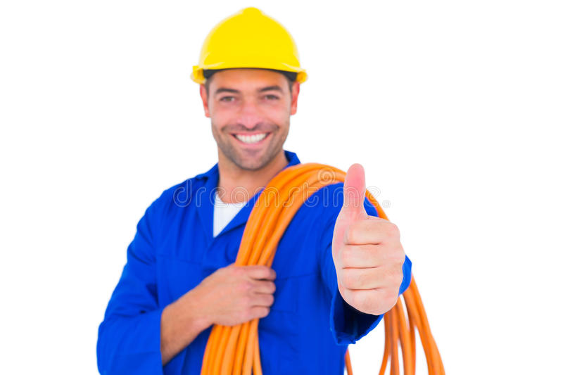 Electrician with rolled wire gesturing thumbs up royalty free stock photo