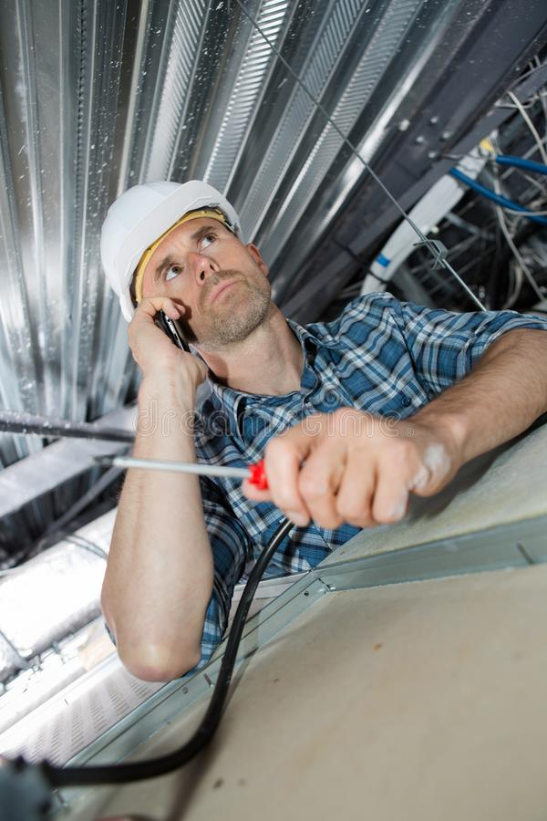 Electrician in roof space taking phone call stock photography