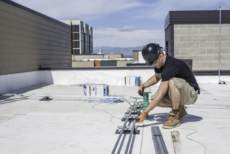 Electrician Running Wire. Through conduit on a building roof top stock photo