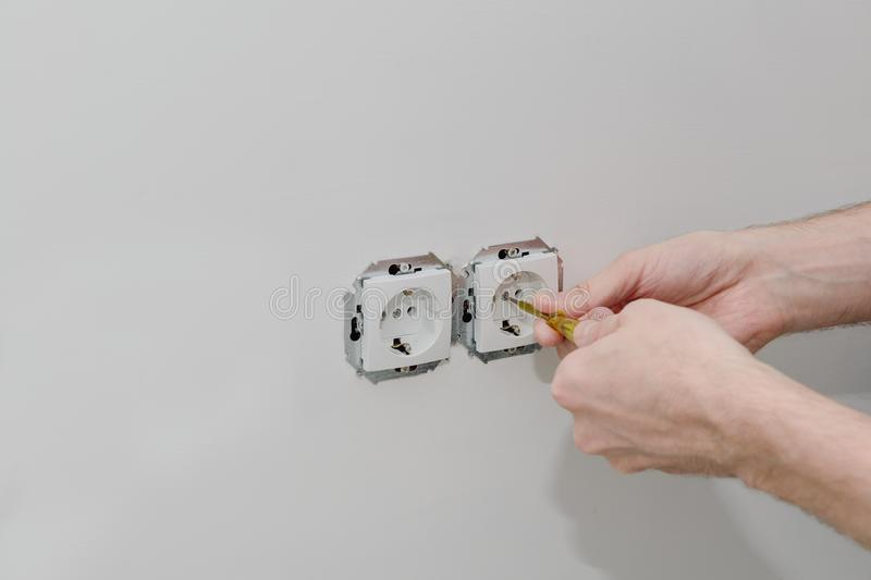 Electrician`s hands are installed socket. Electrician`s hands are installed with a screwdriver royalty free stock photo